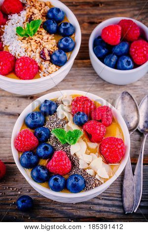 Mango Smoothie Bowls With Raspberries, Blueberries, Chia Seeds And Granola