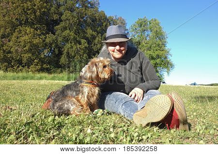 woman sitting with a dog on the grass
