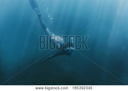 Young woman free diver swimming underwater in deep sea with mask and snorkel.