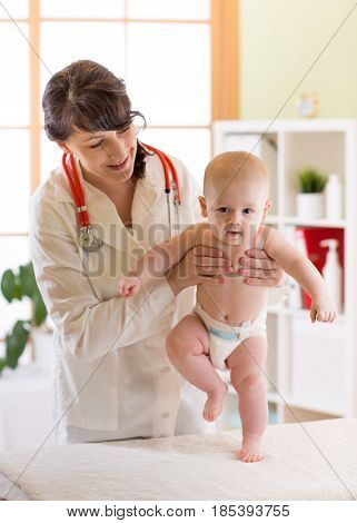 Pediatrician examining cute baby boy. Female doctor testing walking reflex