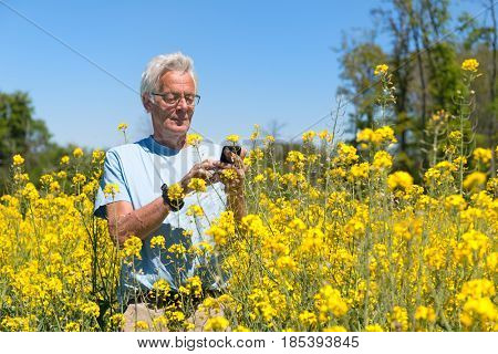 Senior man with mobile phone in yellow colza field
