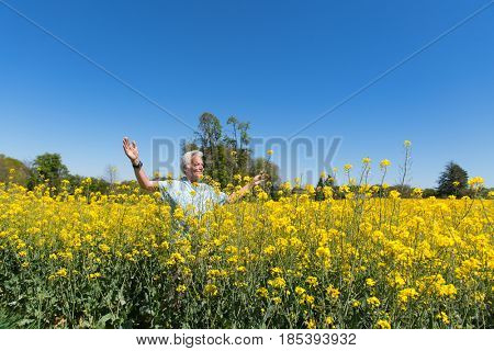 Senior man having freedom in yellow colza field