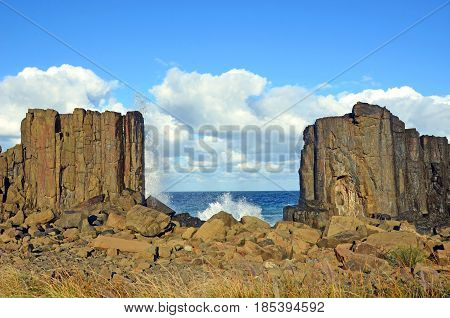 Waves breaking in the gap between basalt rock formations with a view to the sea at Bombo Headland quarry, New South Wales coast, Australia