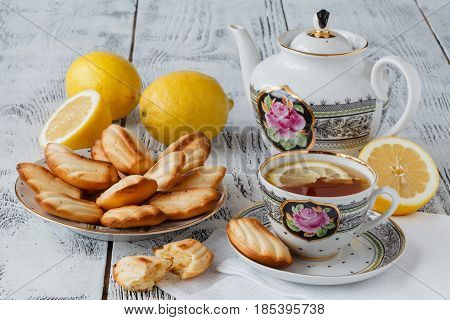 Homemade Madeleines / French Tea Cake Cookies Served In A Floral Plate With Cup Of Tea