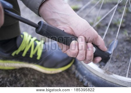 Male inflates bicycle wheel with a pump. Close-up