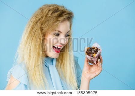 Sweet food sugar make us happy. Attractive blonde woman holds yummy chocolate cupcake in hand open mouth craving for cake.