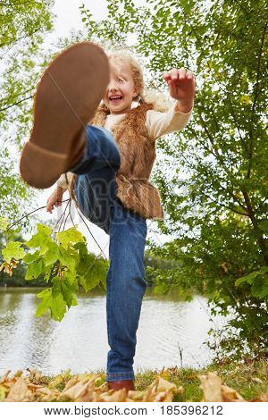 Child romp in autumn in the nature and kicks the leaves