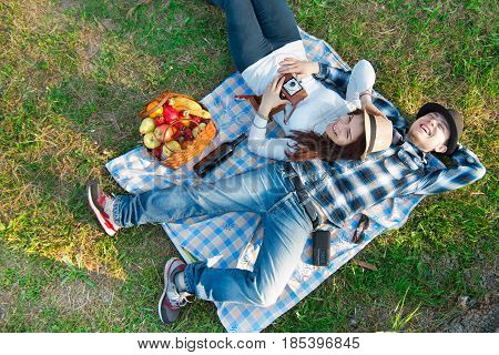 couple in love picnic in park smiling lying down on meadow top view