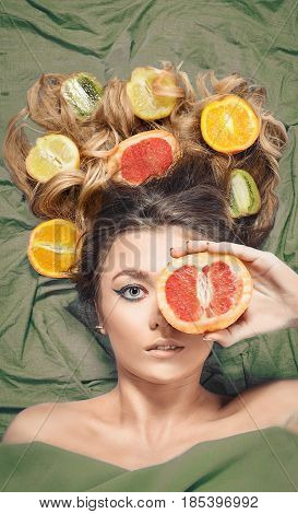 Beautiful gorgeous model girl with colorful citrus healthy fruits in her shiny hair. Care and hair products. Hair care concept. Hair nutrition. Attractive girl with fruits. Natural beauty. Skin care.
