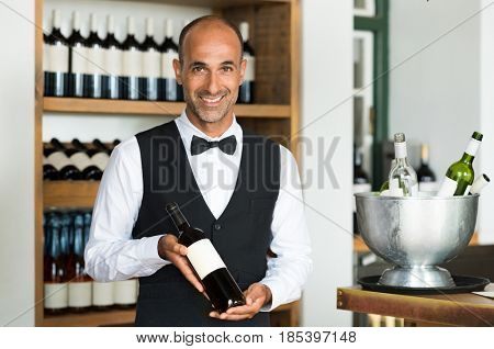 Portrait of a handsome sommelier standing in a wine store and holding a bottle of wine. Confident man in waistcoat and bow tie showing wine bottle at bar counter and looking at camera.