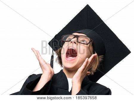 Portrait of a surprised graduate little girl student in a black graduation gown, hat and eyeglasses, looking up with wide open mouth - isolated on white background. Educational concept.