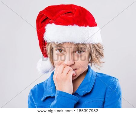 Emotional portrait of attractive caucasian little girl wearing Santa Claus red hat. Funny cute shy child 10 year old looking at camera on gray background. Winter holiday christmas concept.