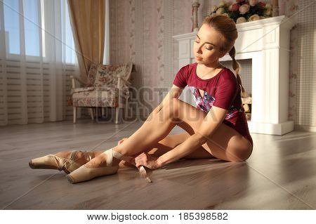 Beautiful Legs Of Young Ballerina Who Puts On Pointe Shoes Sitting On Wooden Floor, Top View With Co