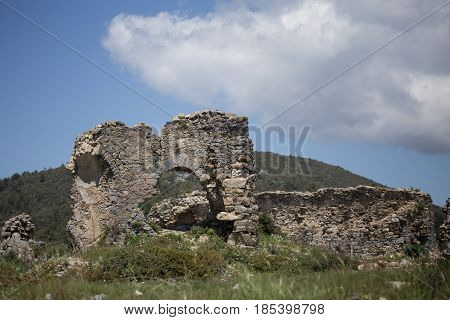 Ruins of historical archeological and natural site Antiochia ad Cragum with remains of ancient building in sharp focus and mountain behind it blurred