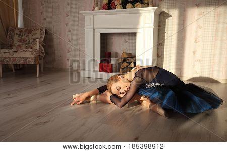 Portrait Of A Professional Ballet Dancer Sitting On The Wooden Floor In Sun Light. Ballet Concept.