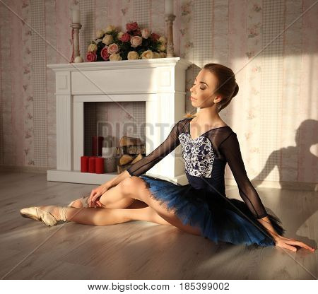 Portrait Of A Professional Ballet Dancer Sitting On The Wooden Floor In Sun Light. Female Ballerina