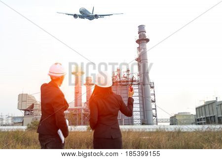 Engineer wearing white helmet holding paper drawing with oil refinery background.