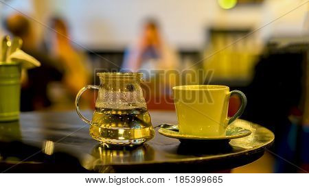 Cup of coffee or tee, glass teapot of hot water, cafe in the morning. Image with blur in low key. Concept lifestyle