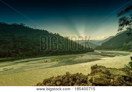 Nice sunset over a turn of river called Tista or Teesta Himalayan Mountain range in the background. River Tista is flowing through Sikkim and source of water for many people in Sikkim India.