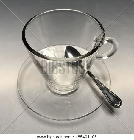 Glass tea cup and saucer on white linen tablecloth
