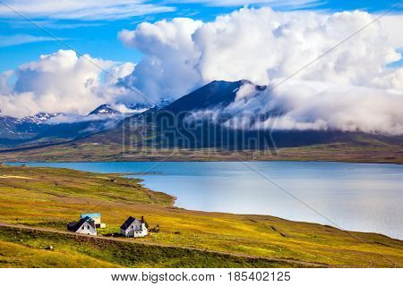 Rhyolitic mountains with not thawed snow on bank of the fjord. Little Farm on the shores of fjord in Iceland. The concept of extreme northern tourism