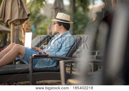 Young Asian man using laptop computer for outdoor working at resort digital nomad lifestyle concepts
