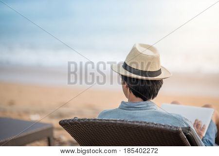 Young asian man sitting on bench at tropical beach and looking to the sea for relaxation after work digital nomad lifestyle or working outdoor concepts
