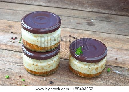 Lard with meat in a jar on a wooden background.