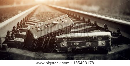 Two old fashioned forgotten a suitcases lie on railroad tracks
