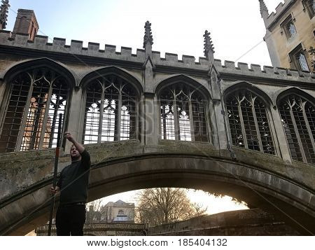 CAMBRIDGE - FEBRUARY 18, 2017: Punting under the Bridge of Sighs on the River Cam between buildings of St John's College at The University of Cambridge in Cambridge, Cambridgeshire, UK.