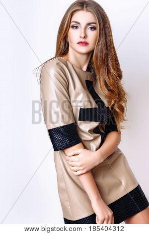 Fashion Portrait Of Beautiful Young Woman With Long Hair. Girl In A Beige With Black Dress On A Whit