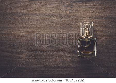 Perfume bottle over wooden background. Perfume bottle on the table. Men's perfume bottle with copy space. Square shaped perfume bottle