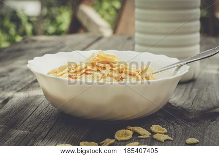 Bottle of milk and bowl of cornflakes on the table. Breakfast concept with cornflakes. Bowl of cornflakes on the table in backyard with some cornflakes scattered