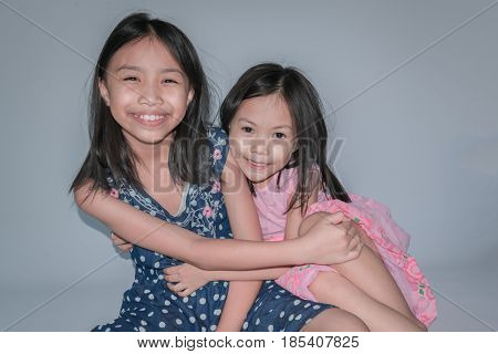 Beautiful Little Child And Her Sister Are Smiling And Showing Confidence On Gray Background. Concept