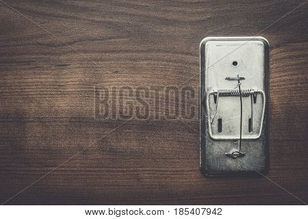 empty mousetrap on the wooden table background
