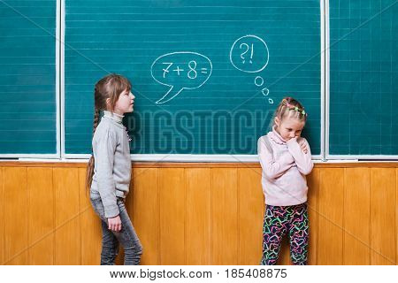 One girl, standing at the school board, assigns a mathematical task to another girl who can not solve it