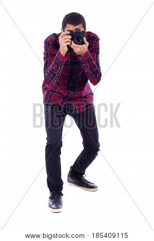full length of a happy young photographer taking a photo guy wearing red caro shirt and jeans isolated on white background