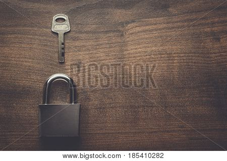 check-lock and key on the brown wooden table background