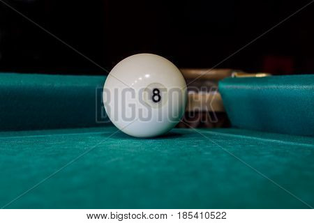 billiard eight ball before the pocket in the corner