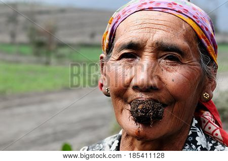 BROMO JAVA INDONESIA - MARCH 26: The ethnic woman living in the area of the Bromo volcano is sitting on the volcanic ash with the tobacco in the mouth during the eruption. Bromo on March 26 2011.
