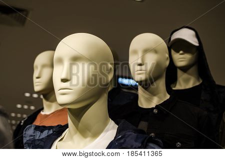 Four heads of male mannequins in a dark style without brand names
