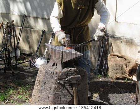 Blacksmith manually forging the molten metal with hammer on the anvil . Photo taken during outdoor public event (no ticket required) in public place . Pistoia Italy