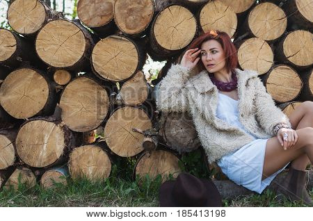 portrait of beautiful redhaired girl in a fur coat sitting on logs. copyspace