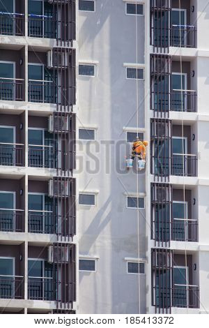 Climber worker hanging on ropes to painting of high rise building