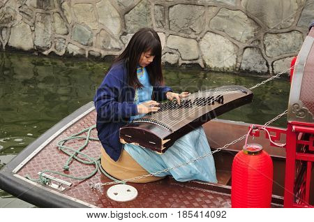 April 27 2016. Beijing China. A chinese woman sitting on a boat playing a traditional chinese instrument guzheng also known as the Chinese zithe on the water canals near houhai bar street in Beijing China.