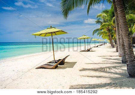 Tropical beach background at Panglao Bohol island with Beach chairs on the white sand beach with blue sky and palm trees. Travel Vacation.