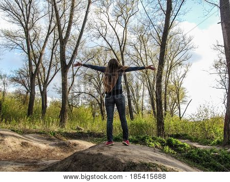 A young girl with long blond hair dressed in navy blue pants and pink sneakers stands on the hillock face to the sky. She spread her arms and enjoys the fresh air in the forest and enjoys life