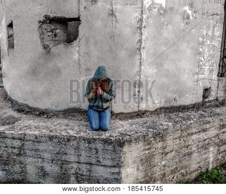 A young woman with long blonde hair in a hood tilted her head and clasped her hands in prayer. The girl prays on her knees near the gray morose wall