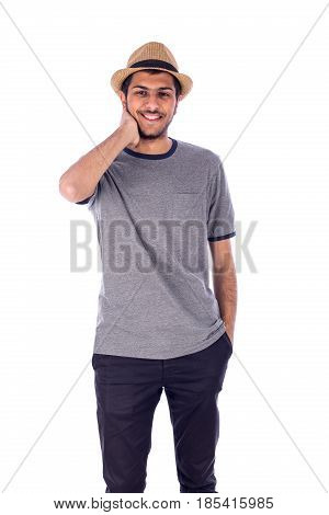 Happy friendly young man with hand in pocket and the other on the neck guy wearing gray t-shirt and jeans with beige hat isolated on white background