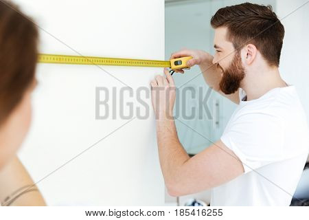 Picture of young cheerful loving couple standing indoors in new flat and make repair. Looking aside.